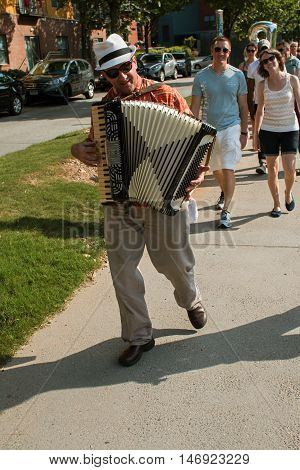 ATLANTA, GA - AUGUST 2016:  An accordion player leads a group of spectators along the Atlanta Beltline to the next stop for the Atlanta Ballet's Wabi Sabi performance in Atlanta GA, on August 6 2016 .