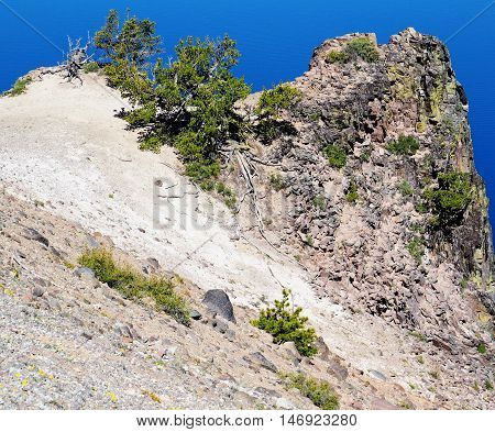 A jagged mass of rock bursts through the crater side of Crater Lake in Oregon.