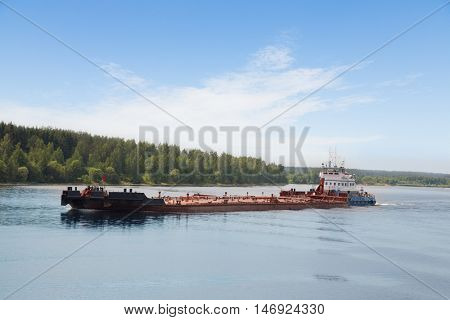 River tugboat moves barge on the Volga River in the summer day