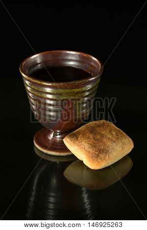Cup of wine and bread on table over dark background