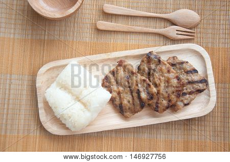 grilled pork with sticky rice on wood plate