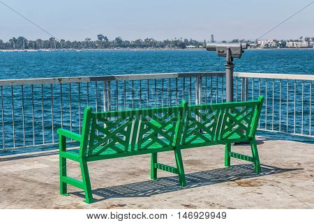 Park bench on the pier at the Cesar Chavez Park in San Diego, California, with Coronado and the San Diego bay in the background.