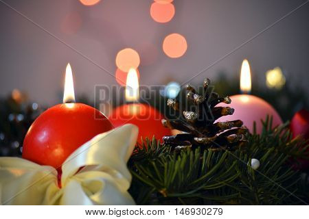 Three Advent Candles against Christmas tree and decorated on the table, in the night time