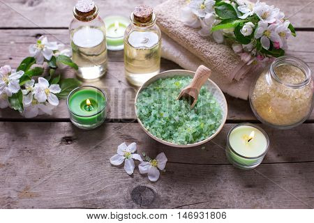 Spa products. Sea salt in bowl towels aroma oil in bottles and flowers on vintage wooden background. Selective focus. Still life.