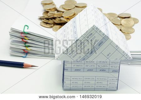 Close Up House With Pencil And Pile Of Gold Coins