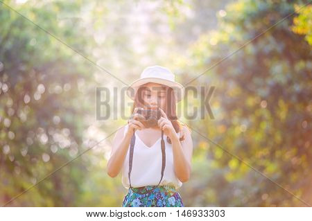 Beautiful asian woman smiling with perfect smile in a park and looking at view screen camera. selective soft focus