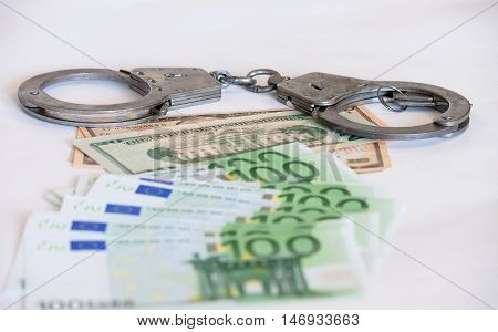 Handcuffs on the money euro and dollars. Economic crime