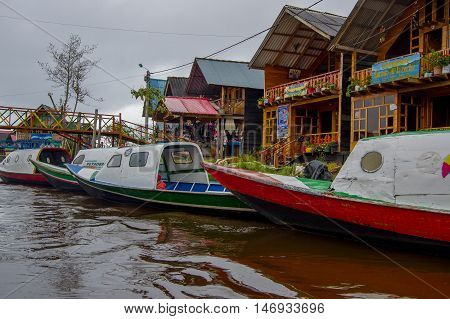 PASTO, COLOMBIA - JULY 3, 2016: colorfull boats parked in front of someshopes located on the shore of la cocha lake.