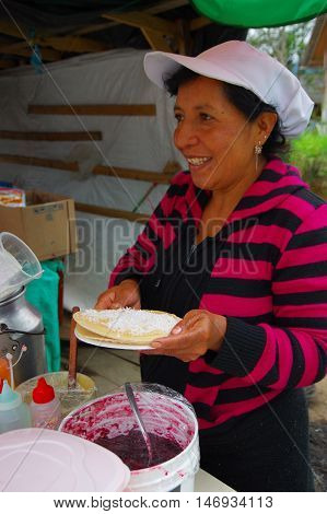 PASTO, COLOMBIA - JULY 3, 2016: unidentified woman preparing a dessert with some wafers, marmalade and coconut.