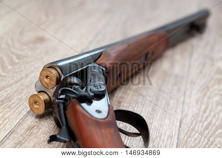 Opened double-barreled hunting gun with two cartridges against black