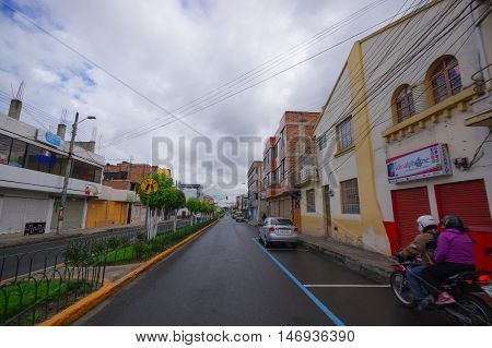 TULCAN, ECUADOR - JULY 3, 2016: man driving a motorcycle with a passenger on a small street of the city.