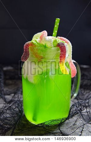 Green drink with ice cream float and gummy worms for Halloween