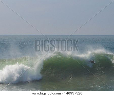 Unidentifiable  body surfer enjoys the big swell at The Wedge in Newport Beach, CA