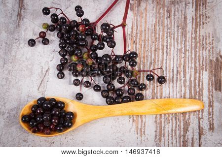 Heap Of Elderberry With Wooden Spoon On Old Wooden Background, Healthy Food