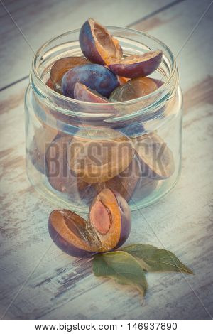 Vintage Photo, Heap Of Plums In Glass Jar On Wooden Table In Garden