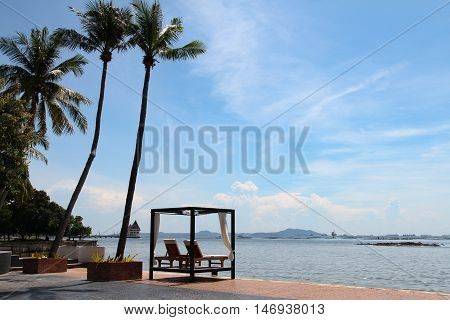 Beach lounge - Sundeck on Sea view for vacation and summer . Seaside spa bed near coconut trees in Pattaya Thailand on holidays .
