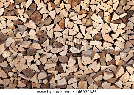 Firewood stacked in wood shed - background