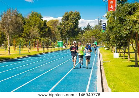 QUITO, ECUADOR - 8 AUGUST, 2016: Blue colored athletic running track located in inner city park La Carolina, runners approaching camera, beautiful sunny day.