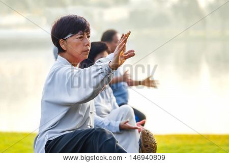 BANGKOK THAILAND - FEBRUARY 13 2016: Unidentified group of people practice Tai Chi Chuan in a park