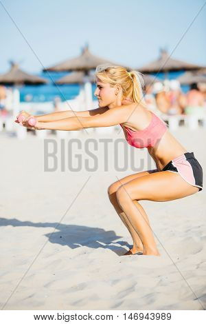 Side view of young athletic woman doing squats on sunny beach