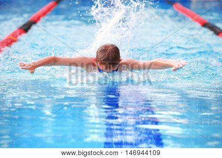 MOTION BLURRED IMAGE, SHALLOW FOCUS,  FOCUS ON WATER IN FRONT OF FACE, Boy swimming Butterfly in a race. MOTION BLURRED IMAGE
