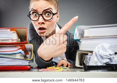 Corporate business concept. Young bureau lady pointing. Nerdy secretary girl making silly face indicating something with finger.