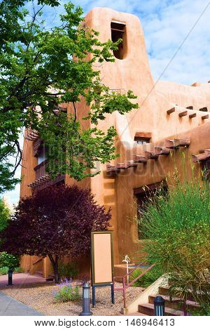 Adobe style building surrounded by lush landscaping taken in Santa Fe, NM