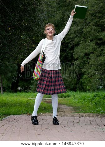 Happy And Funny Schoolgirl In The Park. Girl In School Clothes And Glasses Is Running Out Of The Sch