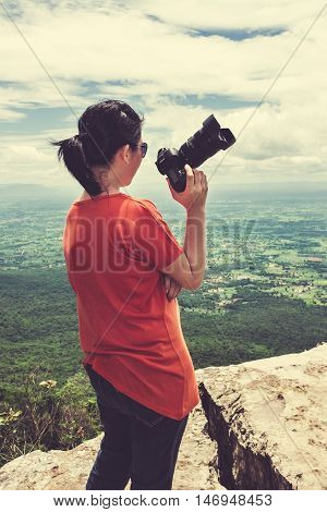 Full body of asian woman with digital camera at view point on the top of mountain travel on vacation. Back view of woman standing against sky with cloudy. Outdoor at the daytime. Cream tone.