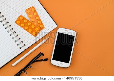 Office desk table with white smart phone,blank spiral notebook, black glasses ,white pencil and orange blisters of pharmaceutical pills on orange table background