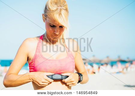 Portrait of serious female runner putting heart rate monitor under sport bra on beach