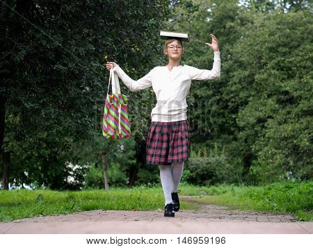 Funny And Happy Schoolgirl In School Uniform In A Park Holding A Book On His Head And Laughs