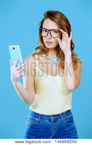 Pretty young woman in spectacles makes selfie on her smartphone. Beauty, fashion.