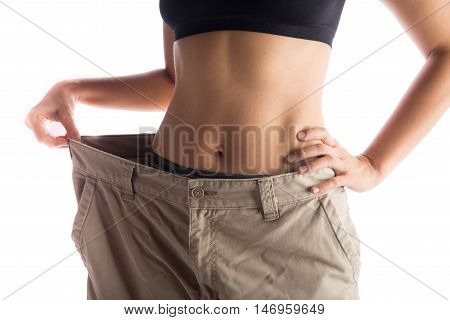 Woman wearing bigger pant after lose weight from work out excercise on white background