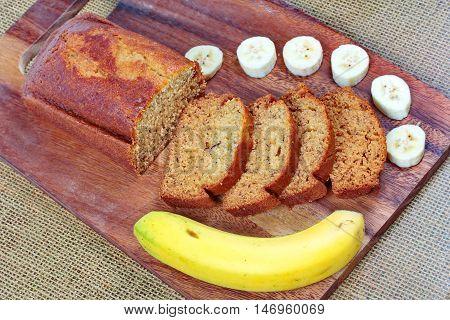 Homemade banana cake with sliced banana and whole banana on butcher served. Side view.