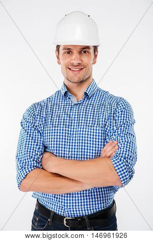 Happy handsome young man builder in hard hat standing with arms crossed over white background