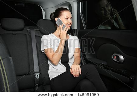 Beautiful business woman sitting in back seat of car