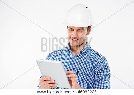 Smiling young man building engineer in helmet using tablet