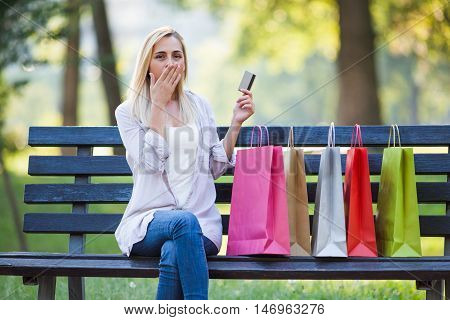 Young woman is sitting in park after shopping. She is nervous because she spent too much money.
