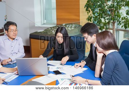 Business meeting Asian people sitting for a table with business plan on high floor in the office. Asian nationality a woman and men watching business graph.