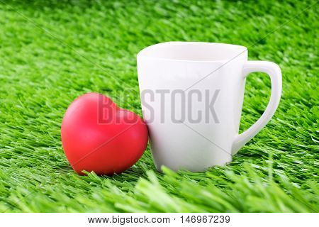 white coffee cup with red heart on green grass