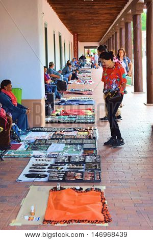 Santa Fe, NM - August 29, 2016:  Native Americans selling their merchandise at the courtyard of the historic adobe style Palace of the Governors Building built in 1610 which has been a government building for centuries taken in Santa Fe, NM.