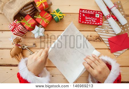 Santa Claus reading letters next to a bag full with presents