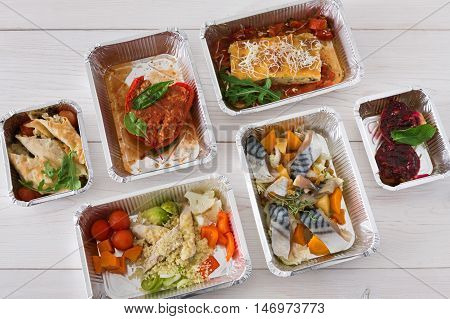 Healthy restaurant food delivery background. Take away of protein and carb balance diet. Fitness nutrition in foil boxes. Top view, flat lay on white wood. Mackerel fish, vegetables and fruits