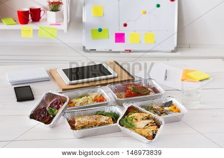 Healthy daily ratio for diet, foil boxes of meat and vegetables with water glass on working table in office. Workspace with mobile phone, papers and tablet. Top view, copy space