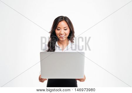 Happy young asian businesswoman standing with laptop isolated on the white background