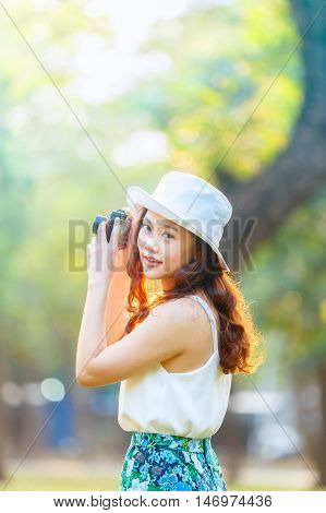 Beautiful asian woman smiling with perfect smile in a park and take a photo by camera in her hand. selective soft focus