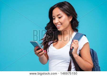 Cheerful young vietnamese girl with backpack using smartphone isolated on a blue background