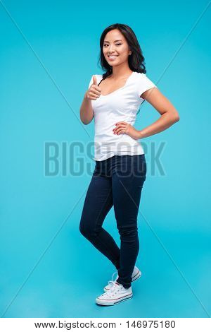 Full length portrait of a young happy asian woman pointing at camera isolated on the blue background