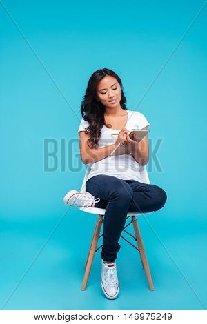 Pensive concentrated young asian woman making notes in notebook while sitting on the chair isolated on a blue background